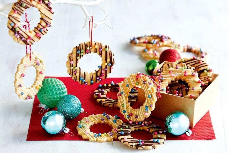 Appendere i biscotti di Natale decorati, decorazione con glassa e palline commestibili