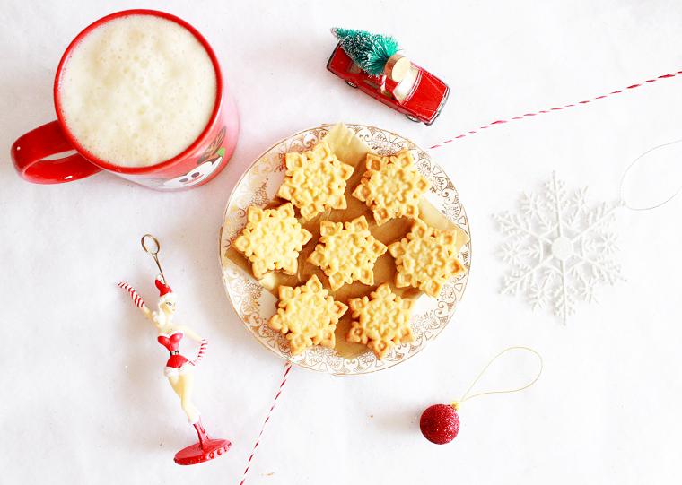 Biscottini forma fiocchi di neve molto semplici, tazza rossa a tema natalizio con un caldo cappuccino
