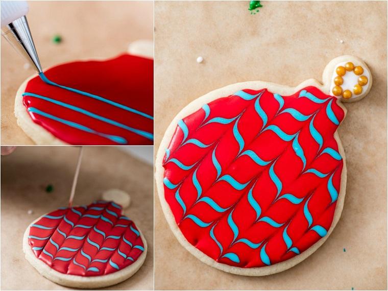 Biscotti di Natale, biscotto forma pallina decorata con della glassa reale e colorante alimentare rosso e motivi a zig zag in azzurro