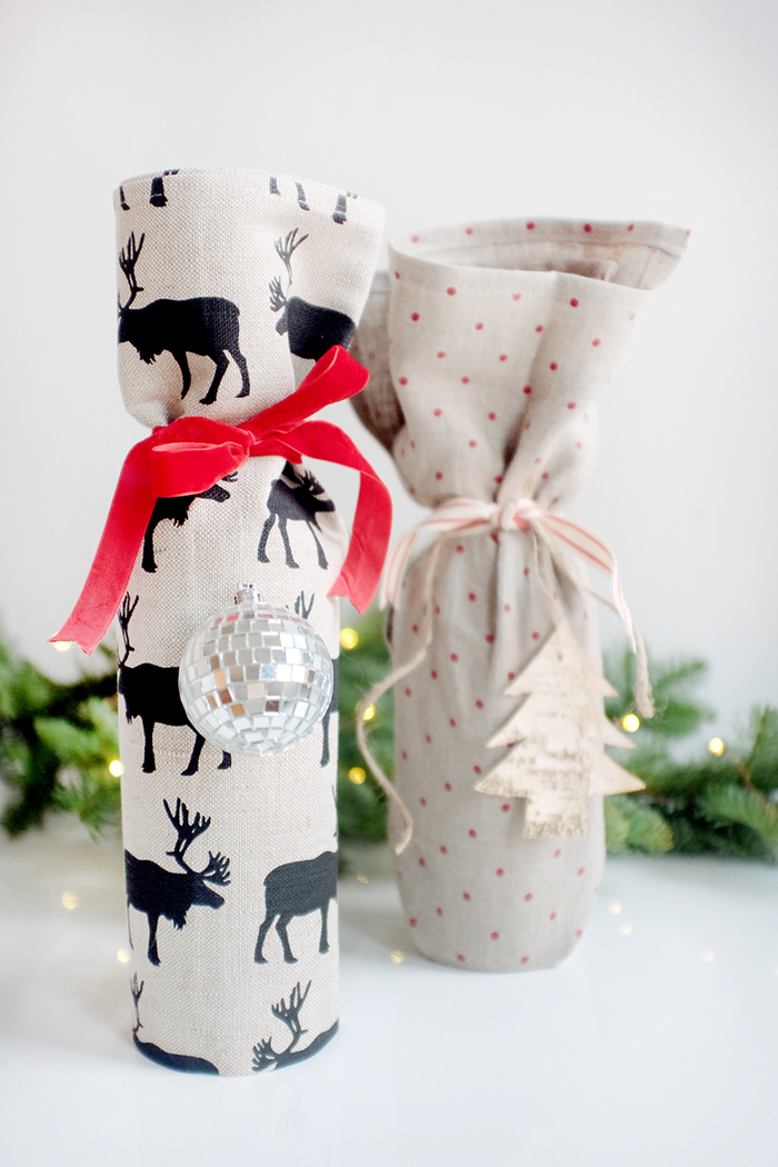sacchetto-colorato-decorazioni-natalizie-pallina-albero-nastro-rosso-bottiglie-di-vino