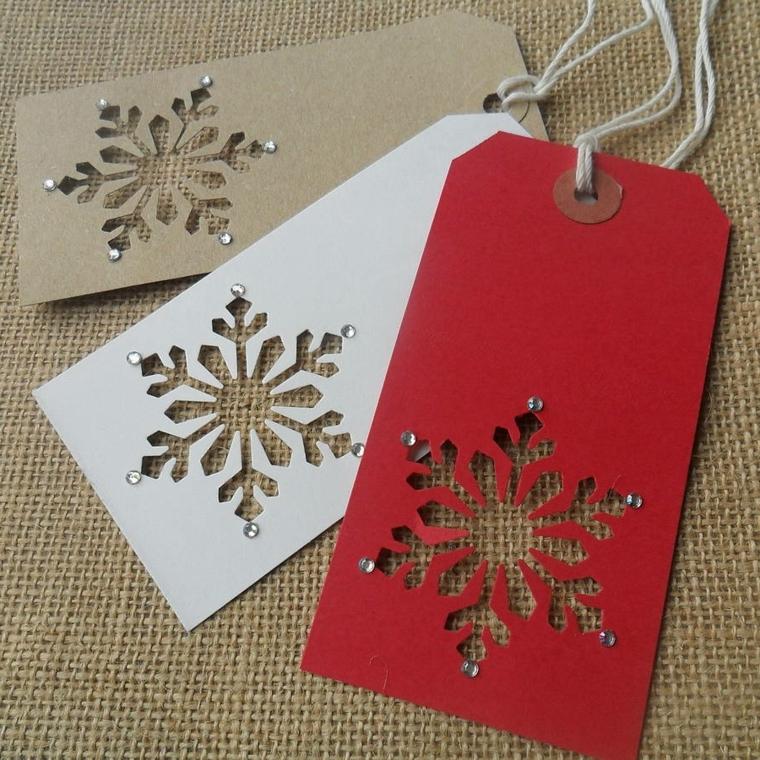 regali di natale fai da te, dei segnalibri in cartoncino con colori diversi, con impresso un fiocco di neve e dei brillantini