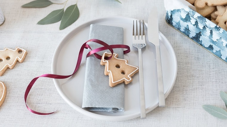 Decorare la tavola a Natale con dei segnaposto originali, biscottini a forma di un albero di Natale con nastro rosso legato al tovagliolo