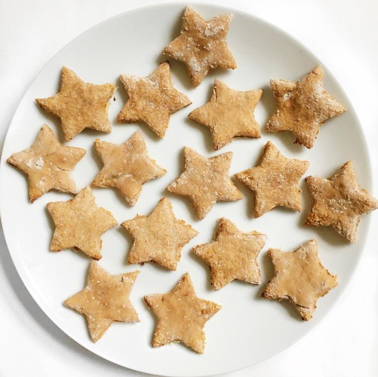 Ricetta semplice per preparare dei biscottini di Natale, forma stelle in un piatto di porcellana bianco