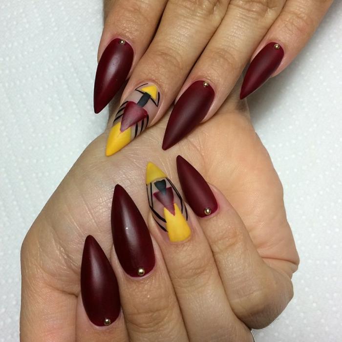 stiletto-medio-forma-punta-colore-bordeaux-piccoli-brillantini-accent-nail-unghia-decorata-giallo-base-trasparente