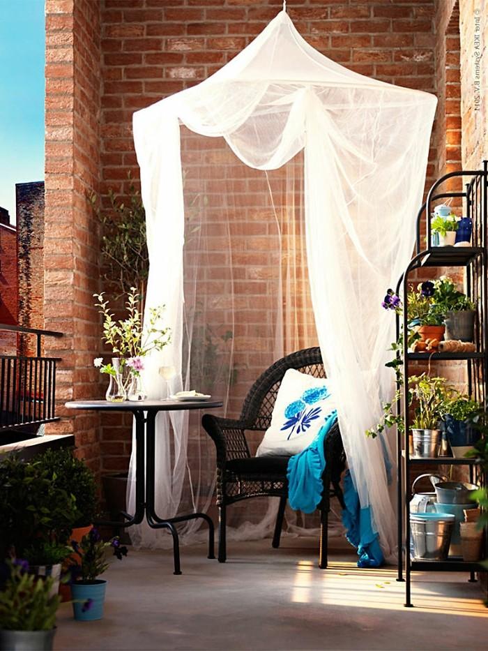 terrazzo-piccolo-parete-mattoni-tavolino-ferro-sedia-rattan-rete-bianca-mobiletto-piante