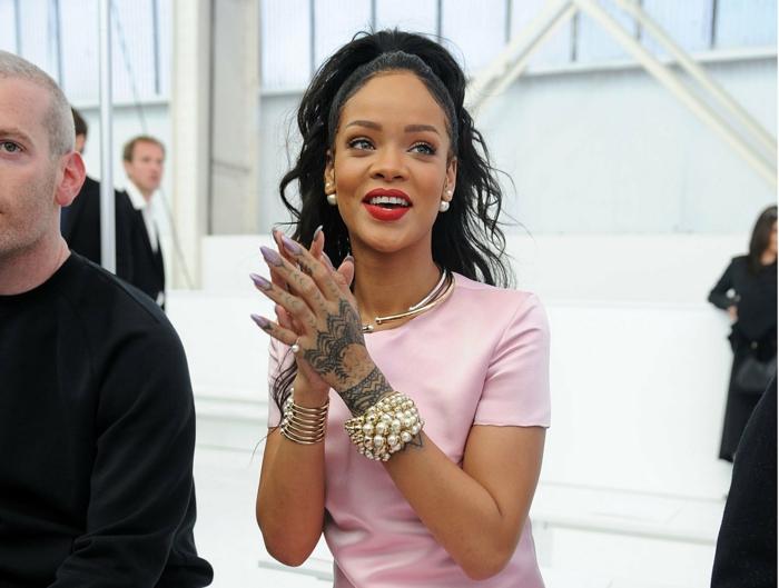 unghie-a-punta-color-viola-chiaro-Rihanna-tatuaggio-mano-braccialetti-perle-capelli-legati-maglietta-rosa
