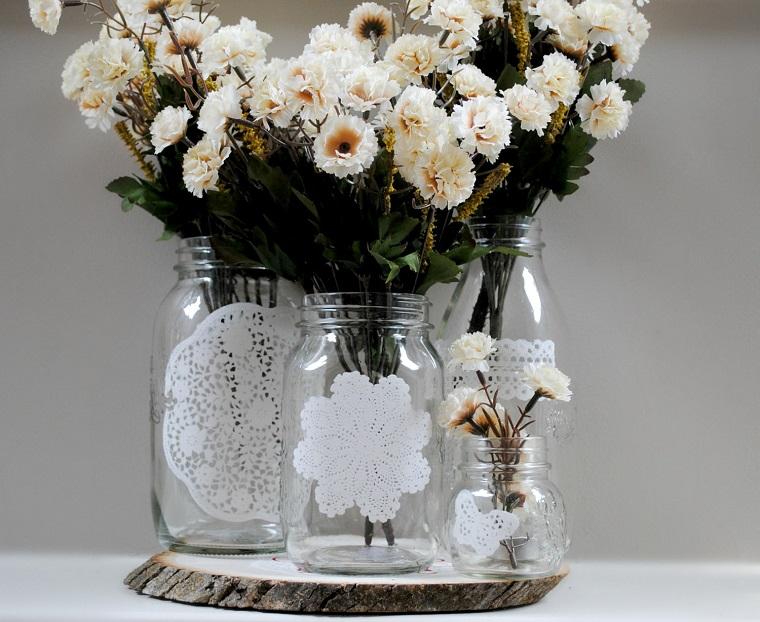 vasi di fiori con barattoli di vetro decorati con centrini centrotavola con tronco di legno
