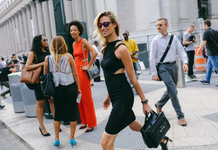 vestirsi-bene-mini-abito-nero-schiena-scoperta-ragazza-capelli-biondi-abbinamento-borsa-nera-pelle-occhiali-da-sole