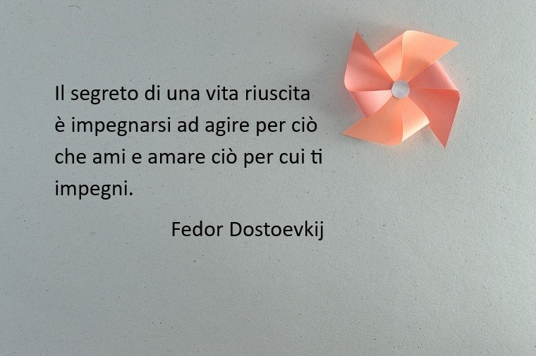 Una frase bellissima di Fedor Dostoevskij sull'amore e sulla vita, sfondo immagine colore grigio con una girandola rosa di carta lucida