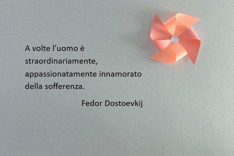 Citazione famosa di Fedor Dostoevskij sull'amore e sulla vita, sfondo grigio e giranodola rosa