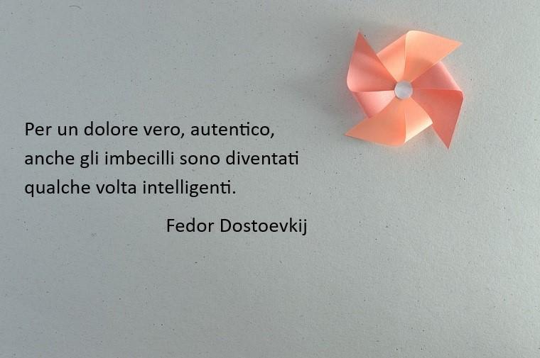 Frase famosa di Fedor Dostoevskij su uno sfondo grigio e una girandola colore rosa