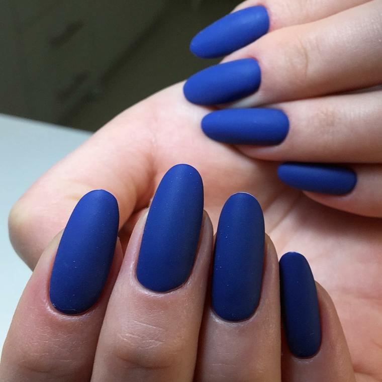 Smalto mat di colore blu, unghie lunghe a forma di mandorla per una donna con la carnagione chiara