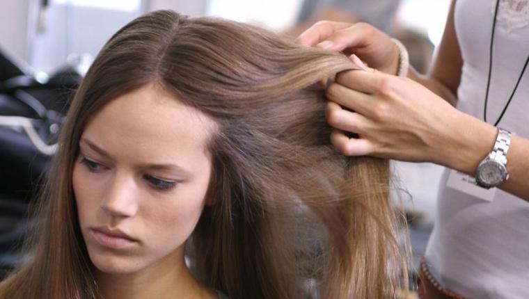 Come prendersi cura dei capelli lunghi di colore castano, messa in piega liscia con riga centrale