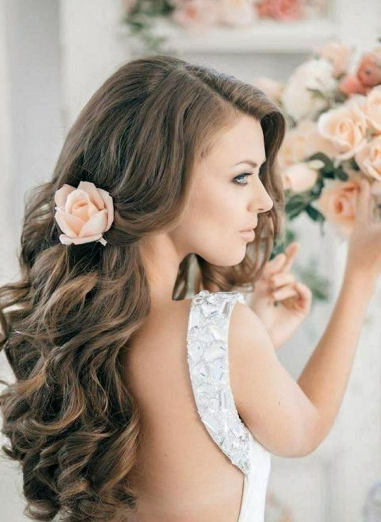Acconciatura sposa con i capelli di colore castano molto chiaro con ricci morbidi e fiore tra i capelli