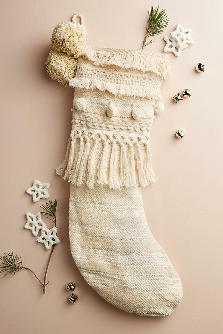 Decori natalizi, calza di maglia di colore bianco con pon pon e piccoli rametti di un sempreverde