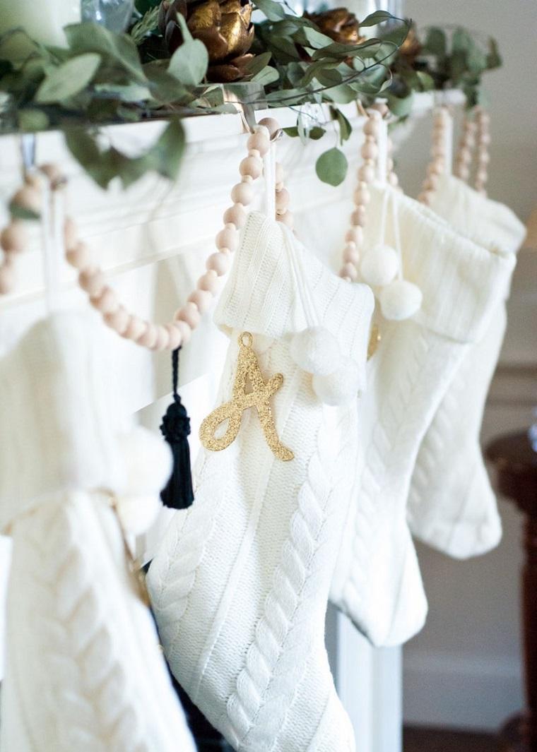 Come addobbare la casa per Natale, calze all'uncinetto di colore bianco con letterina in oro e ghirlanda in legno