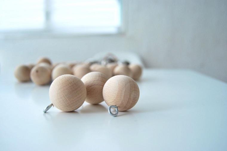 Creazioni natalizie con palline di legno e ganci in metallo per creare una ghirlanda