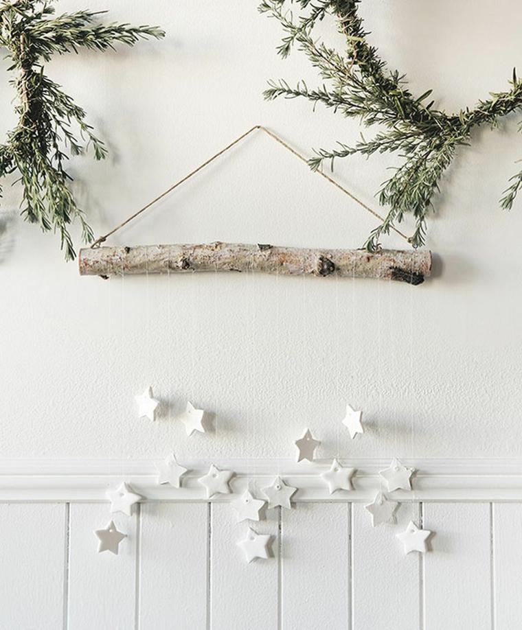 Decorazione da parete con un ramo di legno e stelle appese su fili quasi invisibili