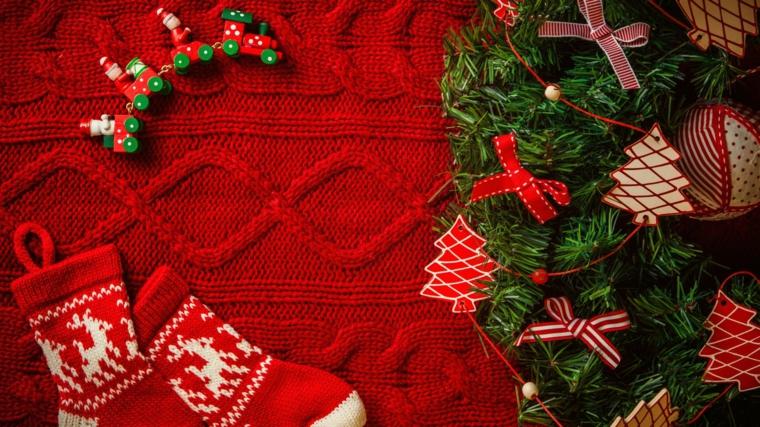 Decorazioni natalizie di stile tradizionale con calze rosse e ghirlanda con addobbi vari