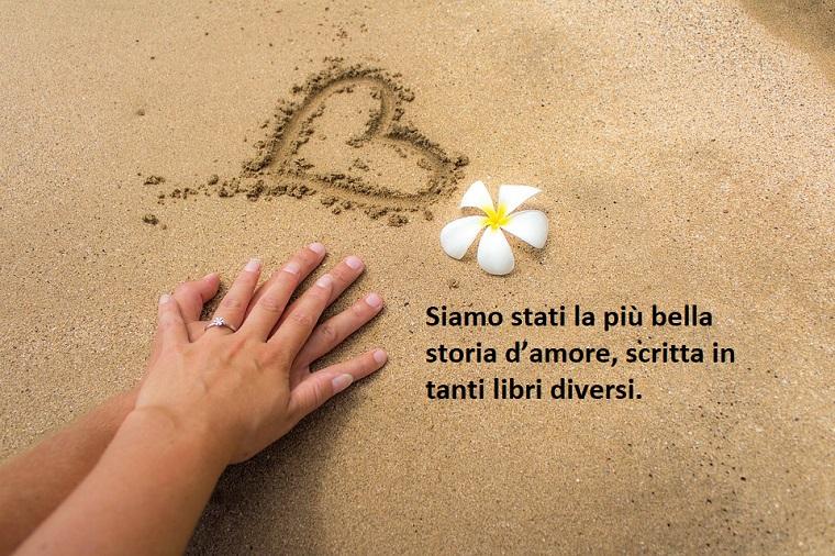 Citazioni amore, scritta romantica sulla sabbia, disegno cuore e due mani