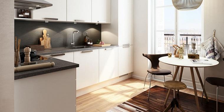 Cucina angolare con ante di colore bianco e top in marmo grigio scuro, set da pranzo con tavolo rotondo