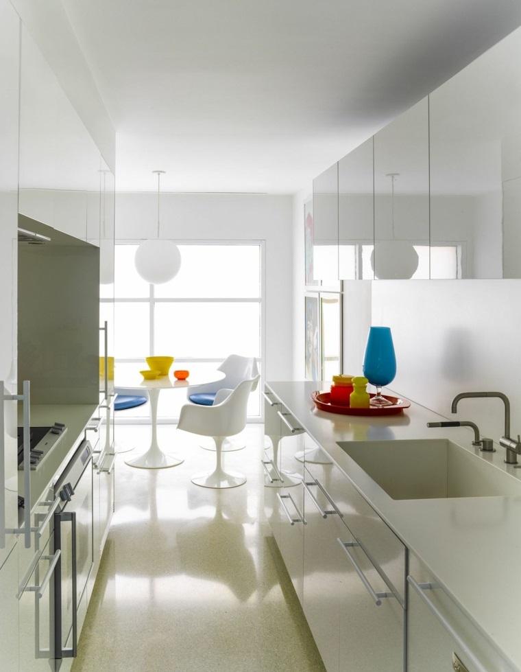 Cucina bianca con superfici dei mobili lucidi, accessori con colori vivaci e un set tavolo da pranzo rotondo