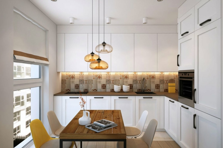 Cucina angolare di colore bianco, top in marmo colore scuro e lampade a sospensione di vetro