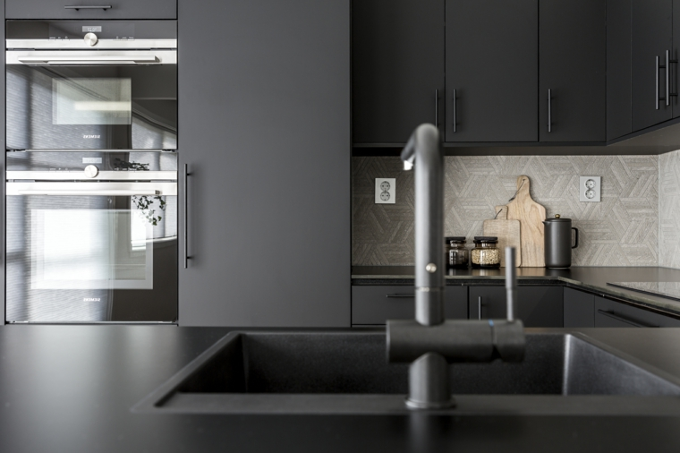 Cucina dal design moderno con superfici di colore nero ed elettrodomestici da incasso