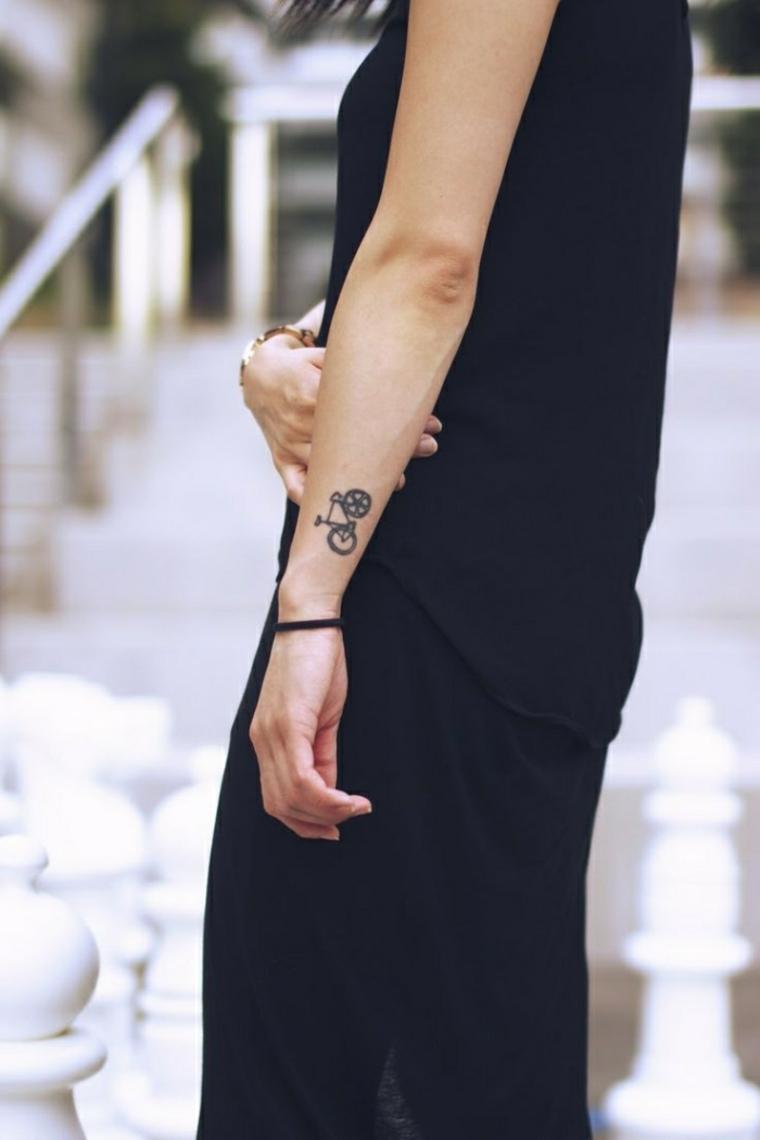 Idea per un tatuaggio femminile da fare sul polso della mano e una piccola bicicletta di colore nero