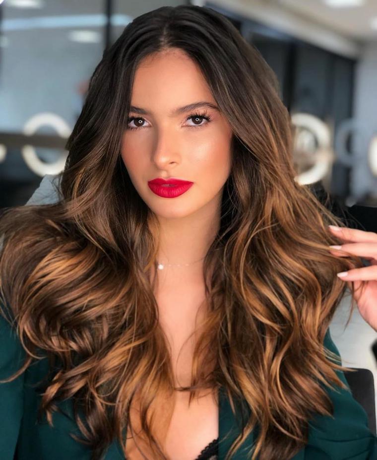 capelli lunghi con frangia scalata donna con pettinatura mossa di colore castano