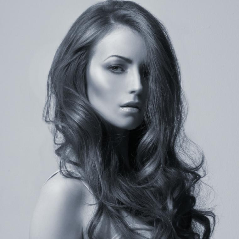 Donna con i capelli lunghi di colore castano con messa in piega mossa e frangia da parte