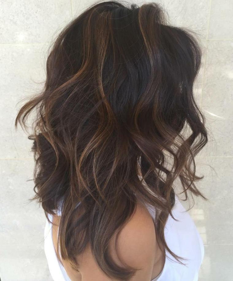 Tagli capelli medio lunghi di colore castano con colpi di sole più chiari e messa in piega mossa