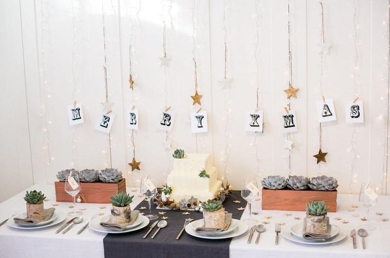 Tavola di Natale, decorazione con due vasi rettangolari con piante grasse e una scritta Merry Xmas