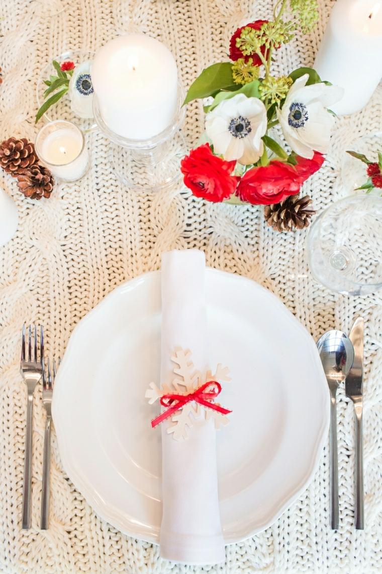 Segnaposto con un fiocco di feltro e fiocco rosso, centrotavola con vaso di fiori, pigne e candele