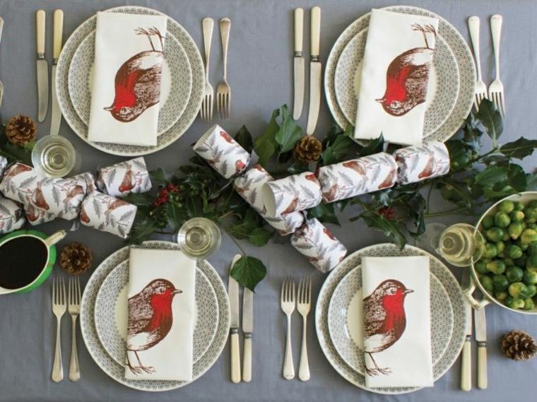 Lavoretti di Natale con pigne, centrotavola con bacche rosse e rami con foglie verdi