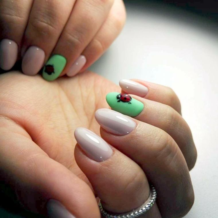 Decorazione con coccinella su una base di colore verde, unghie corte di colore beige a forma di mandorla