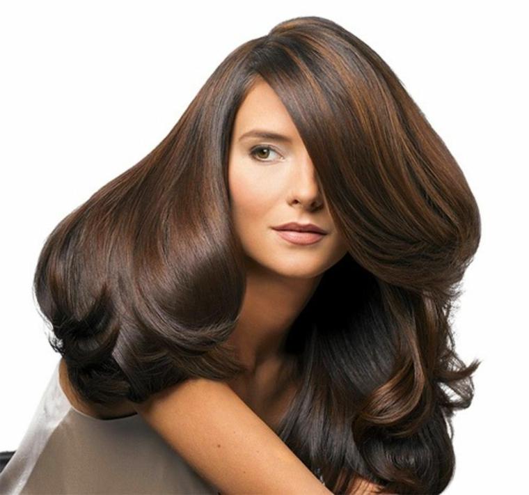 Messa in piega voluminosa per capelli di colore castano con riga laterale