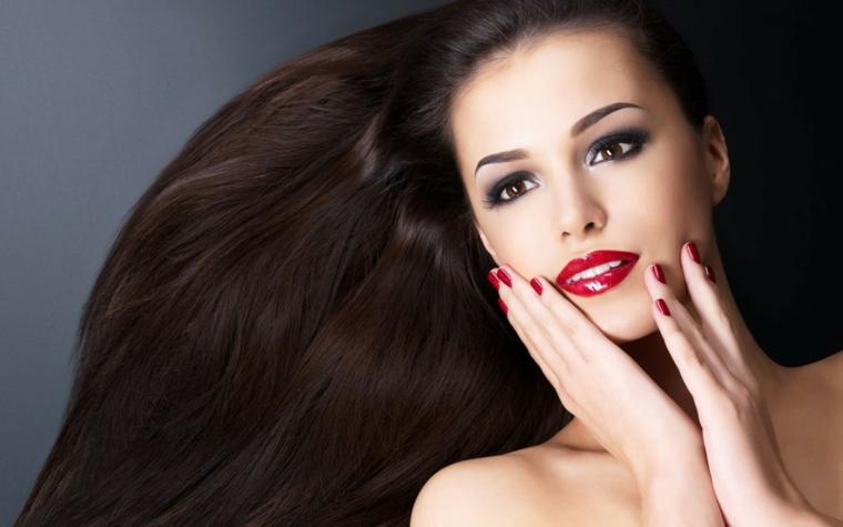 Tagli lunghi e un colore dei capelli castano intenso sul cioccolato in abbinamento al rossetto e allo smalto rosso