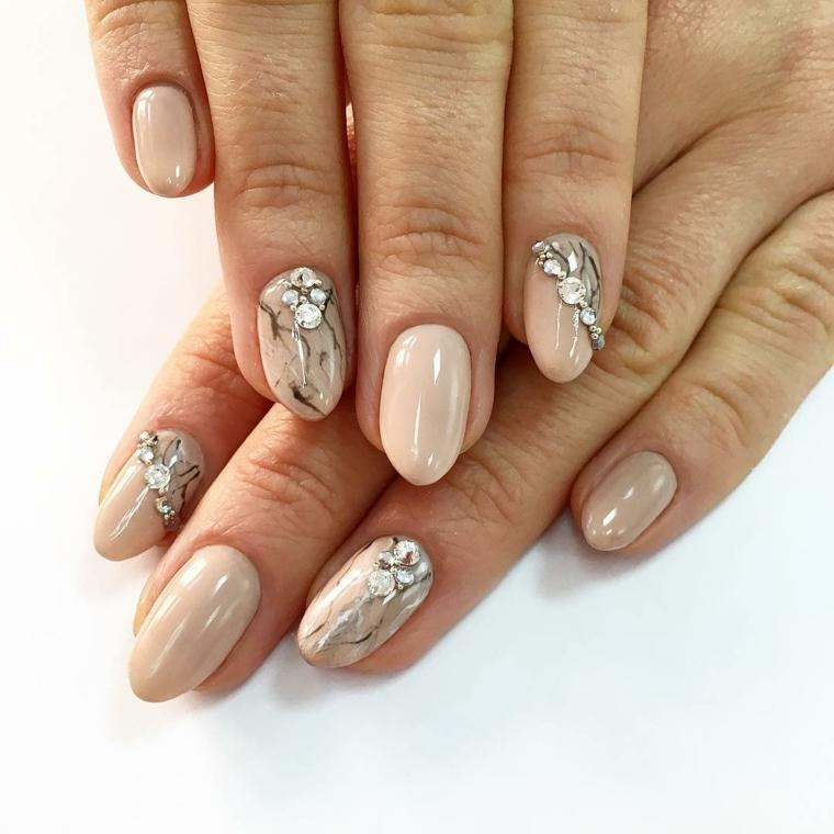 Decorazione effetto marmo su una base color pelle, unghie dalla forma a mandorla di media lunghezza