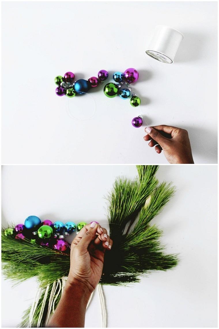 Decori natalizi, palline colorate su filo più sottile e festone con rami di pino