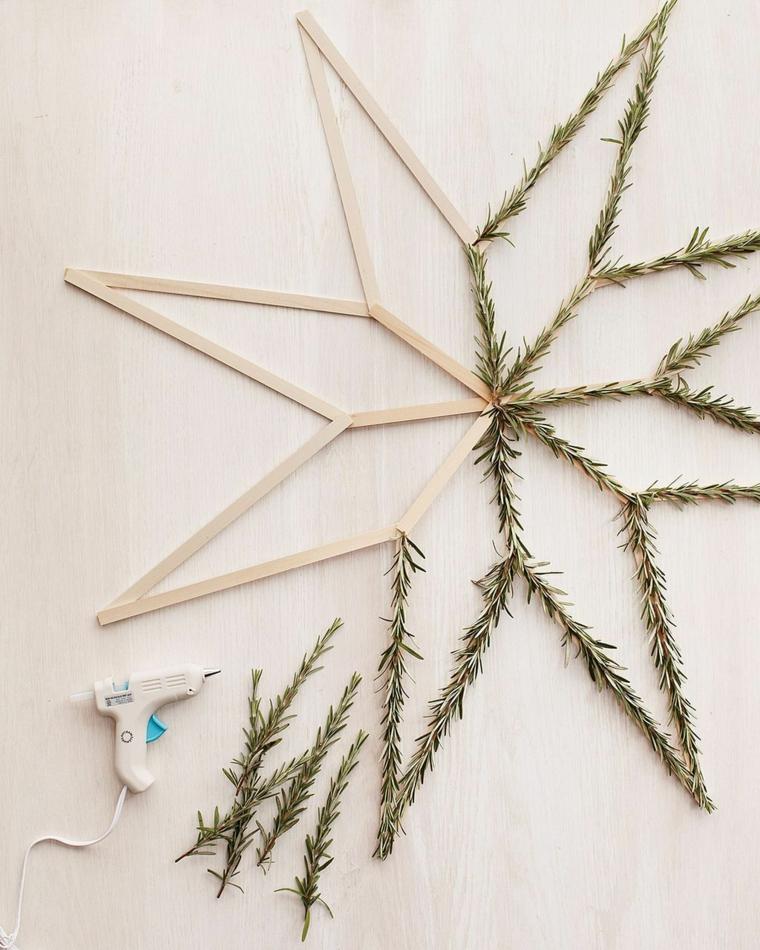 Lavoretti di Natale fai da te, stella in legno con rami di un sempreverde incollati con la pistola colla a caldo