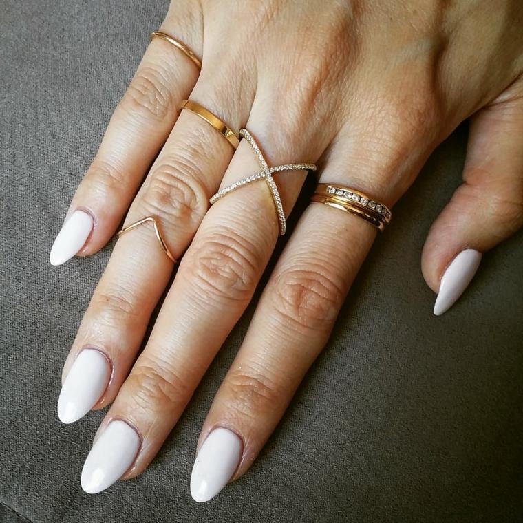 Unghie tonde, smalto color crema per una manicure perfetta in abbinamento agli anelli in oro
