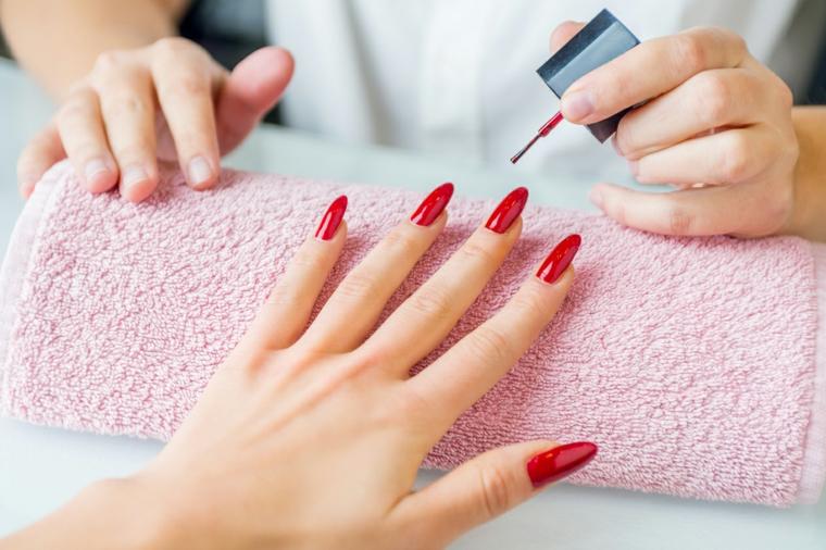 Fare la manicure perfetta sulle mani, smalto di colore rosso molto luminoso per unghie lunghe a mandorla