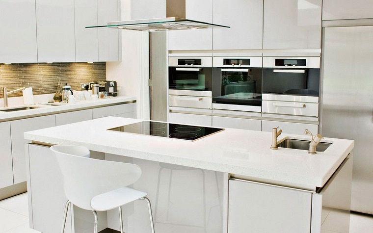Cucina angolare di colore bianco e di design, illuminazione con faretti nascosti e superfici lucide