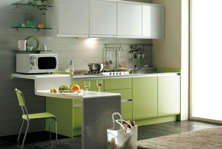 Piccola cucina di colore bianco e verde con isola laterale di vari livelli, ante armadietti superiori colore bianco