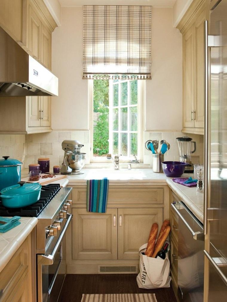 Forma della cucina U con ante in legno di colore beige, la piccola finestra illumina lo spazio