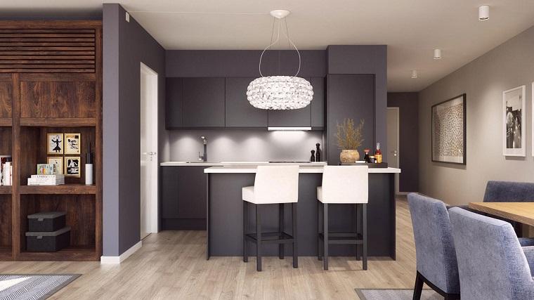 Arredamento open space con mobili dal design moderno e di colore nero, cucina funzionale a vista
