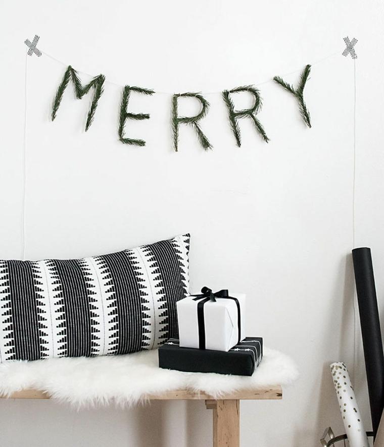 Scritta natalizia realizzata con i rami di un sempreverde, panchina in legno con pacchi regalo in stile scandinavo