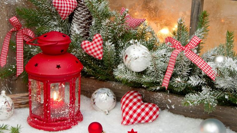 Creazioni natalizie in stile tradizionale con lanterna rossa e ghirlanda di rami con addobbi