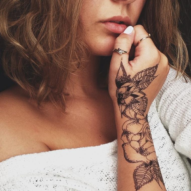 Tatuaggi femminili, donna con un grande tatuaggio sul braccio, inchiostro di colore nero e disegni di fiori con petali